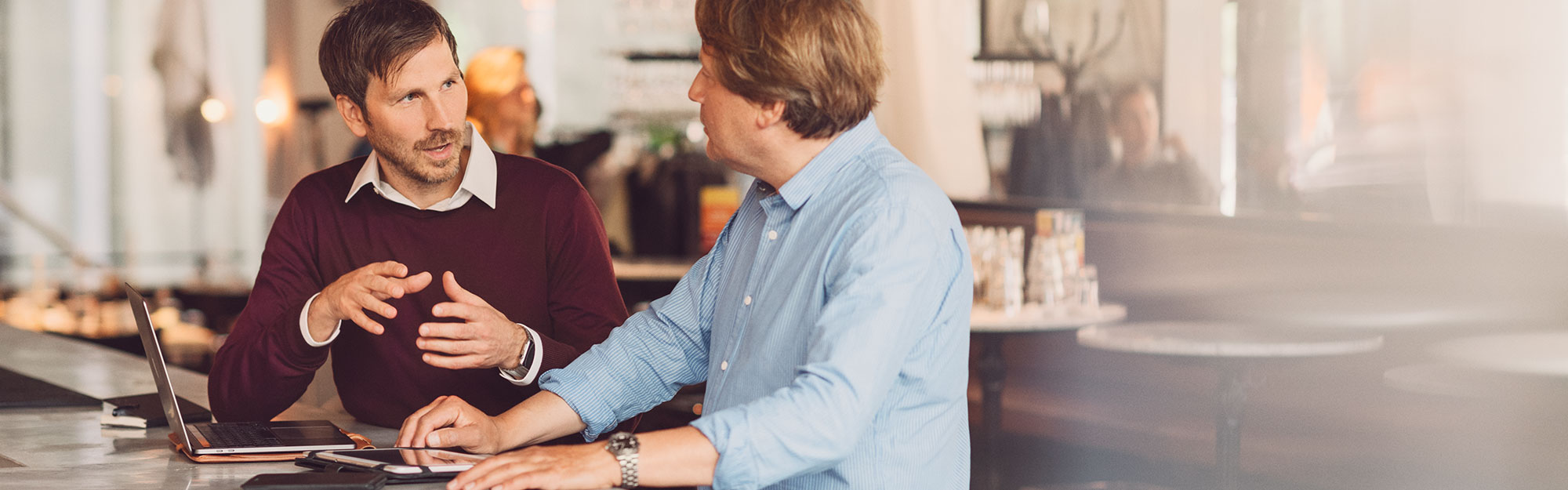 Two businessmen discussing at a counter.